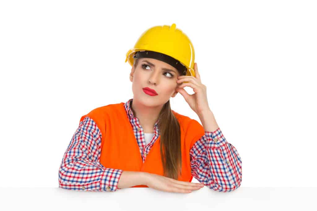 Young woman in yellow hardhat, orange reflective vest and lumberjack shirt leans on a white banner, scrathing head, looking up and thinking. Studio shot isolated on white. thinking over naming strategy pic for Sue-Ann Bubacz post on WriteMixforBusiness
