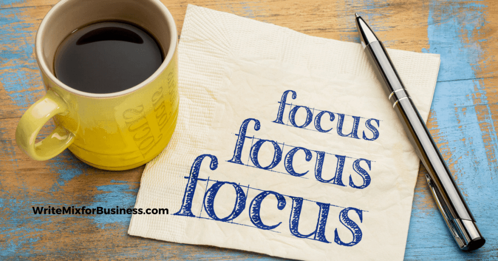 "Focus theme shown with coffee cup and napkin with word ""Focus"" written on it 3 times WriteMixforBusiness.com post by Sue-Ann Bubacz"
